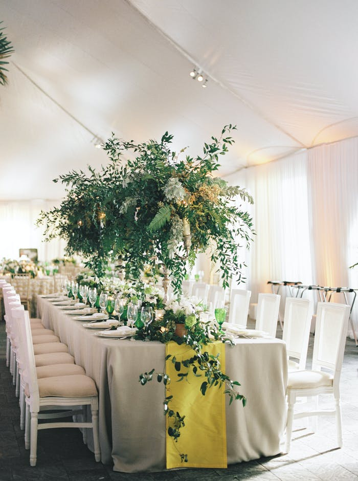 A white tent encapsulates a long rectangle table with a yellow runner and white chairs. Dramatic tall and leafy greenery acts as the centerpiece.