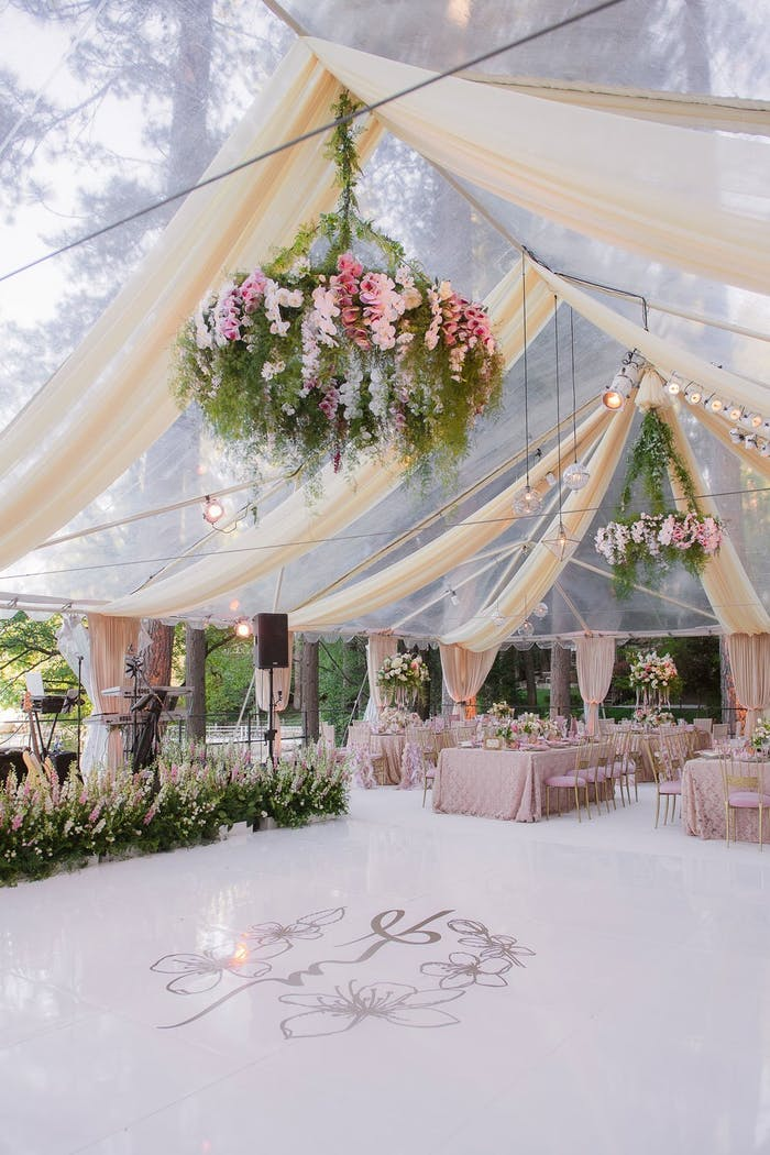 clear tent with gauzy draping and pink and green florals over dance floor