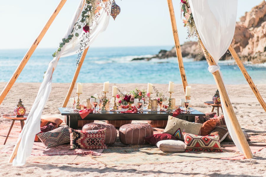 pink, coral and maroon poufs sit on the sand surrounding a low table with tall pillar candles and low florals. There is a wooden tee pee structure over top with white linens blowing in the breeze. The ocean and rocks are in the background.