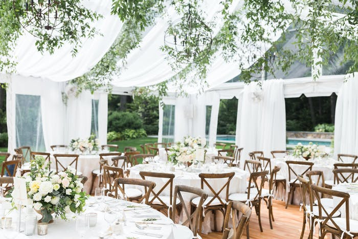 White tented drapery hangs from the top of the ten. Wooden chairs are placed around round tables.
