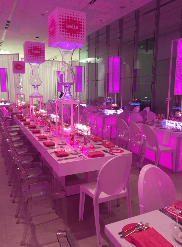 Pink lighting everywhere reflecting off of the ghost chairs and modern white venue.