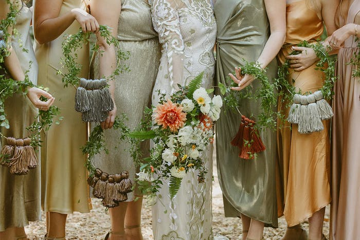 Bridesmaids in shades of green and gold stand together with bouquets in hand.