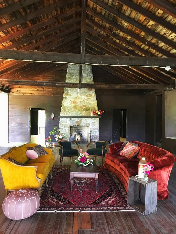 a mustard and fire red couch face each other in a vaulted room with a tall fire place
