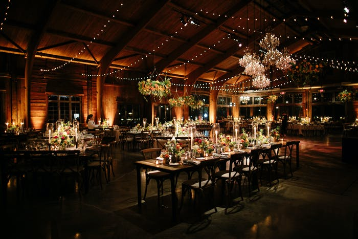 A dark room is filled with warm minimal lighting and chandeliers.