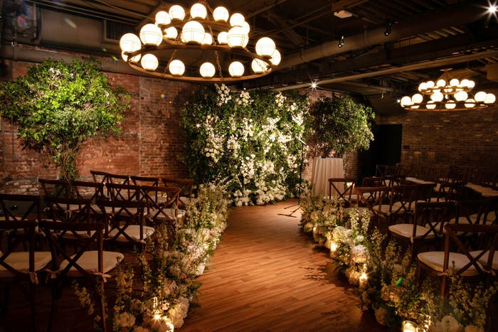 A dimly lit room with stunning chandeliers and large greenery pieces