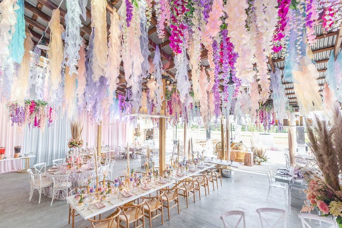 pink florals hang from the ceiling above long rectangle white tables and light wood accenting.