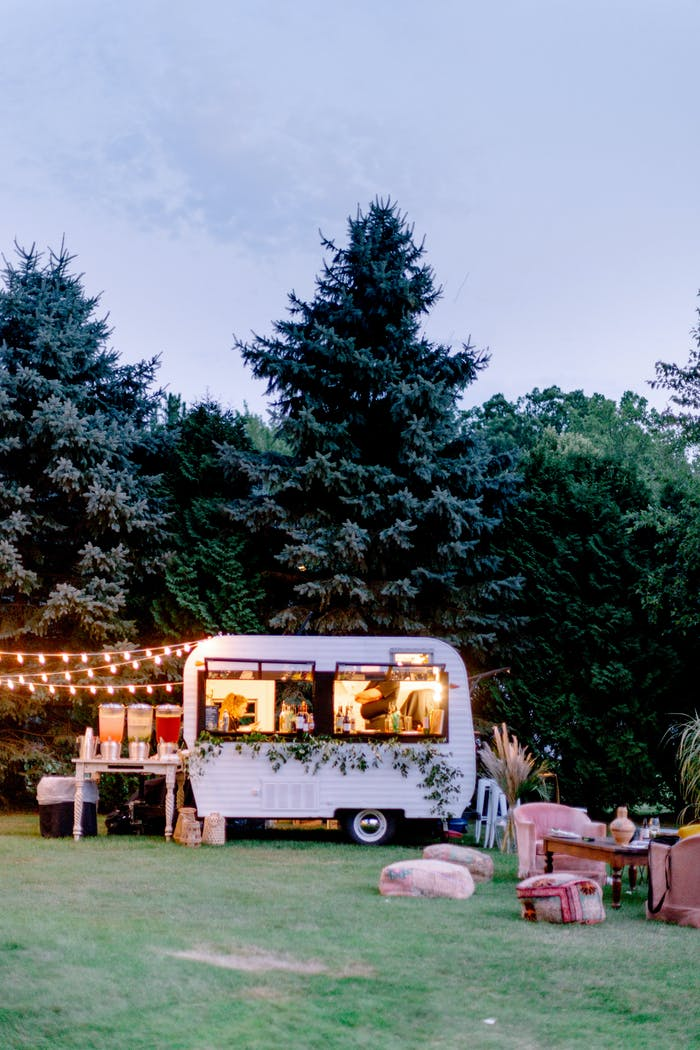 a small trailer is illuminated against dense forest. Fairy lights hang from it and pink furniture is next to it.