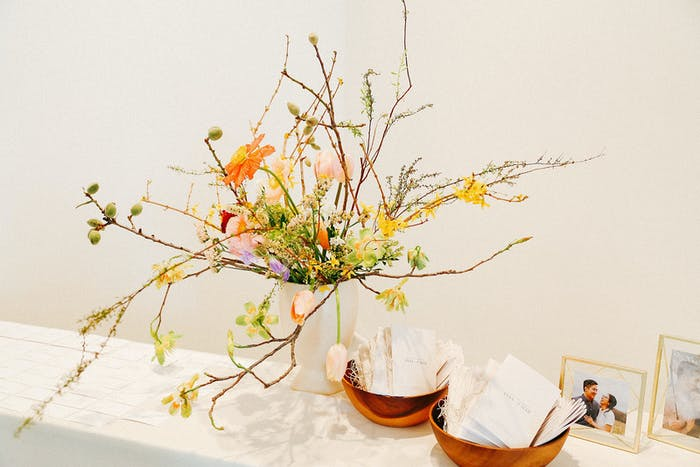 a white background with a white table in the foreground that holds two wooden bowls and a branchy sparse floral arrangement with yellows and oranges. Photos of a couple are tucked behind.