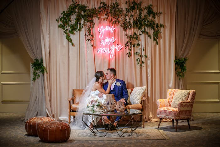 A couple sits in a lounge area with a neon sign and greenery surrounding it. Blush drapes are in the background