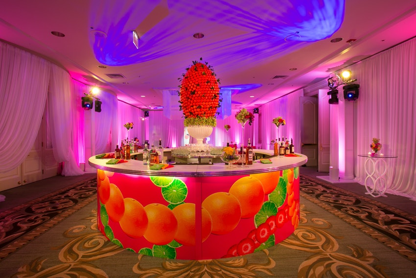 A large colorful focal bar anchored the center of the cocktail space.