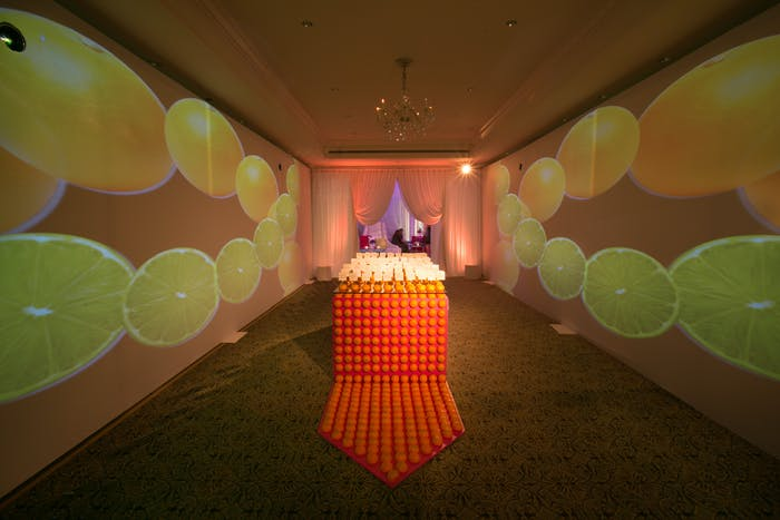 citrus projections flanking fresh orange decorated place card table