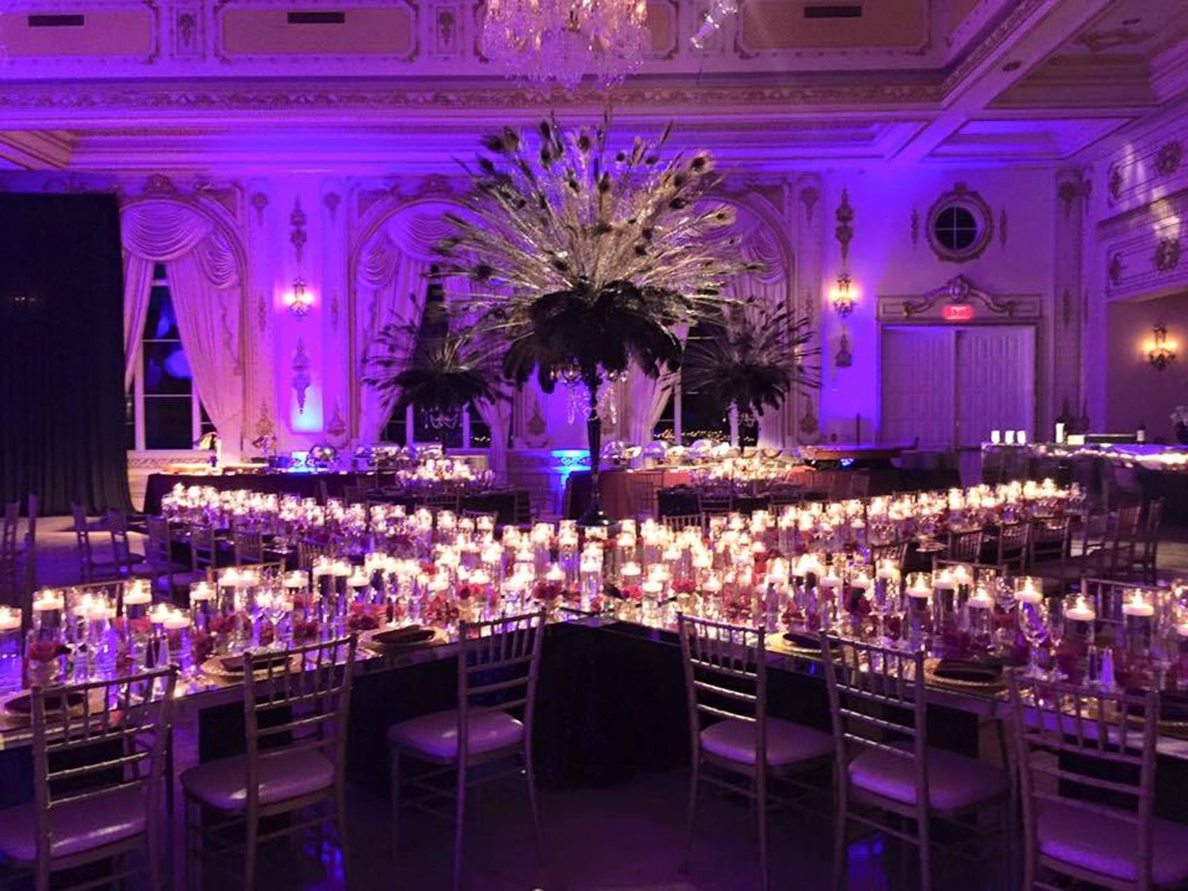 Purple room with tables arranged in x and large peacock feathers in the middle. The tables have candles throughout making them glow.