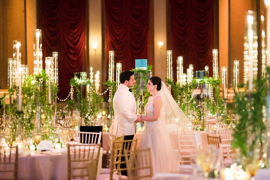 Husband and Wife stand in between tables with candelabras draped in greenery.