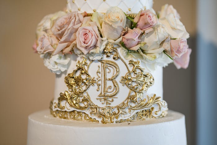 A white cake with gold carving and pink and white florals