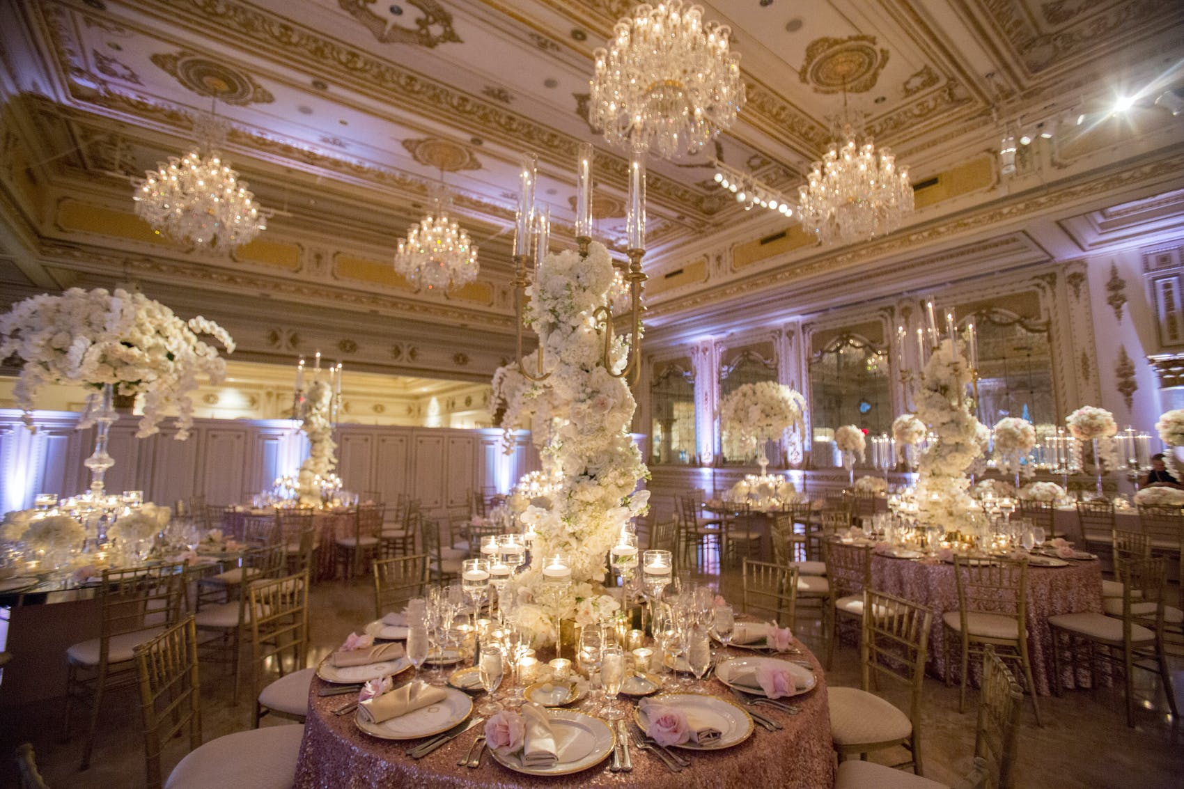 Tables with large large white bouquets in the middle that climb up to the chandeliers on the ceiling