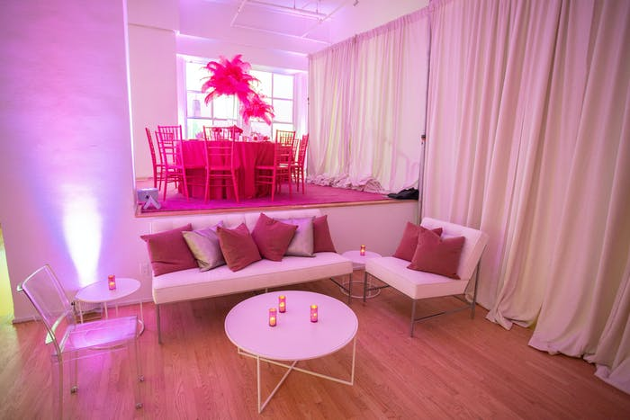 White drapes line a pink lit room with white colors and pink pillows