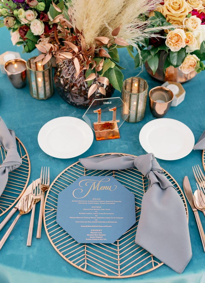A tablescape with pampas grass and yellow florals and geometric accents.