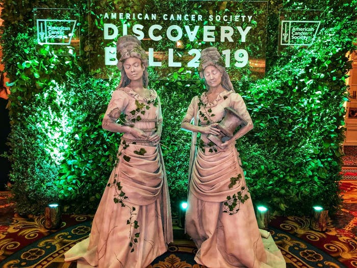 "Two women dressed as statues pose in front of foliage backdrop with ""American Cancer Society Discovery Ball 2019"" signage."