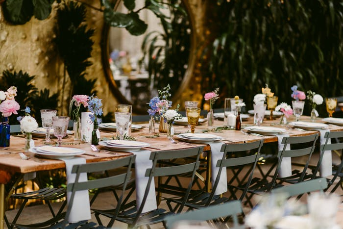 A long table with minimal floral arrangements. White linens hang off the edge.