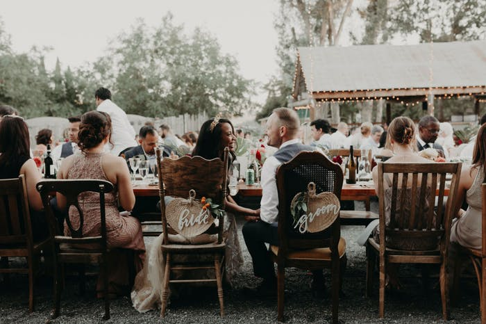 An outdoor reception with mismatched chairs.