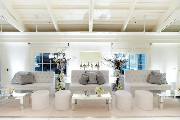 An all white color palette with three couches and four floor poufs
