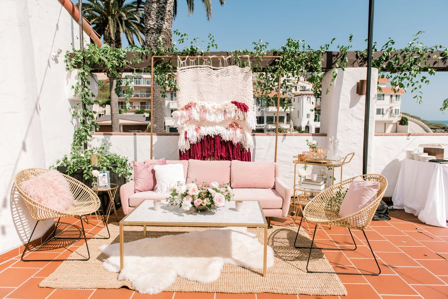 a bright terrace with dessert orange tiling. A powder pink and white rug sits on top with wicker chairs and a couch. A greenery covered pergola sits in the background.