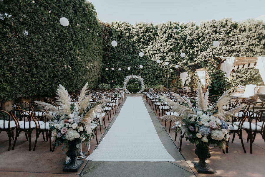 a white linen aisle in the middle of hedges acting as walls. Pampas grass marks the beginning of the aisle and a white floral archway at the end. White globe lights act as lighting for the event.