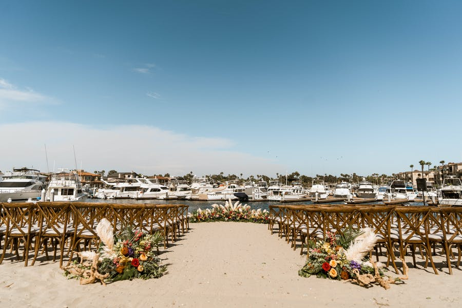 dark wooden chairs on sand lead to the end of the aisle. Big blue sky is in the background.