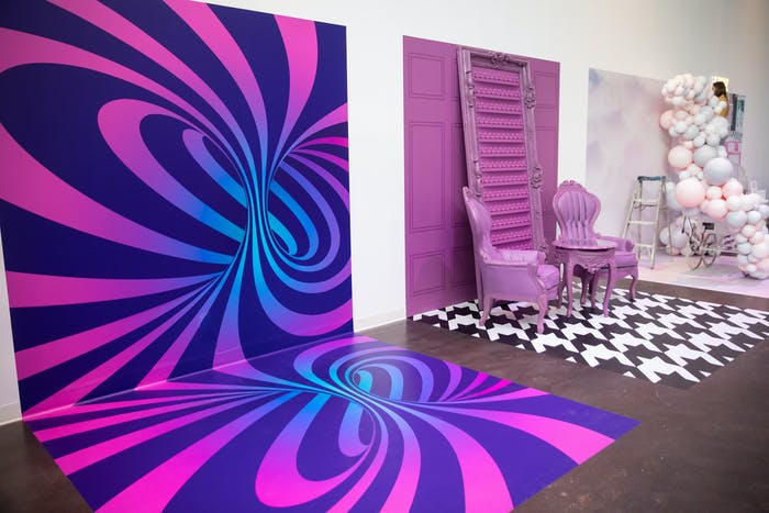 various instagram backdrops along a white wall. The first is a spiral effect that is pink, purple, and blue. the second is a pink barn door with two victorian style chairs and the third is a cloud of balloons.