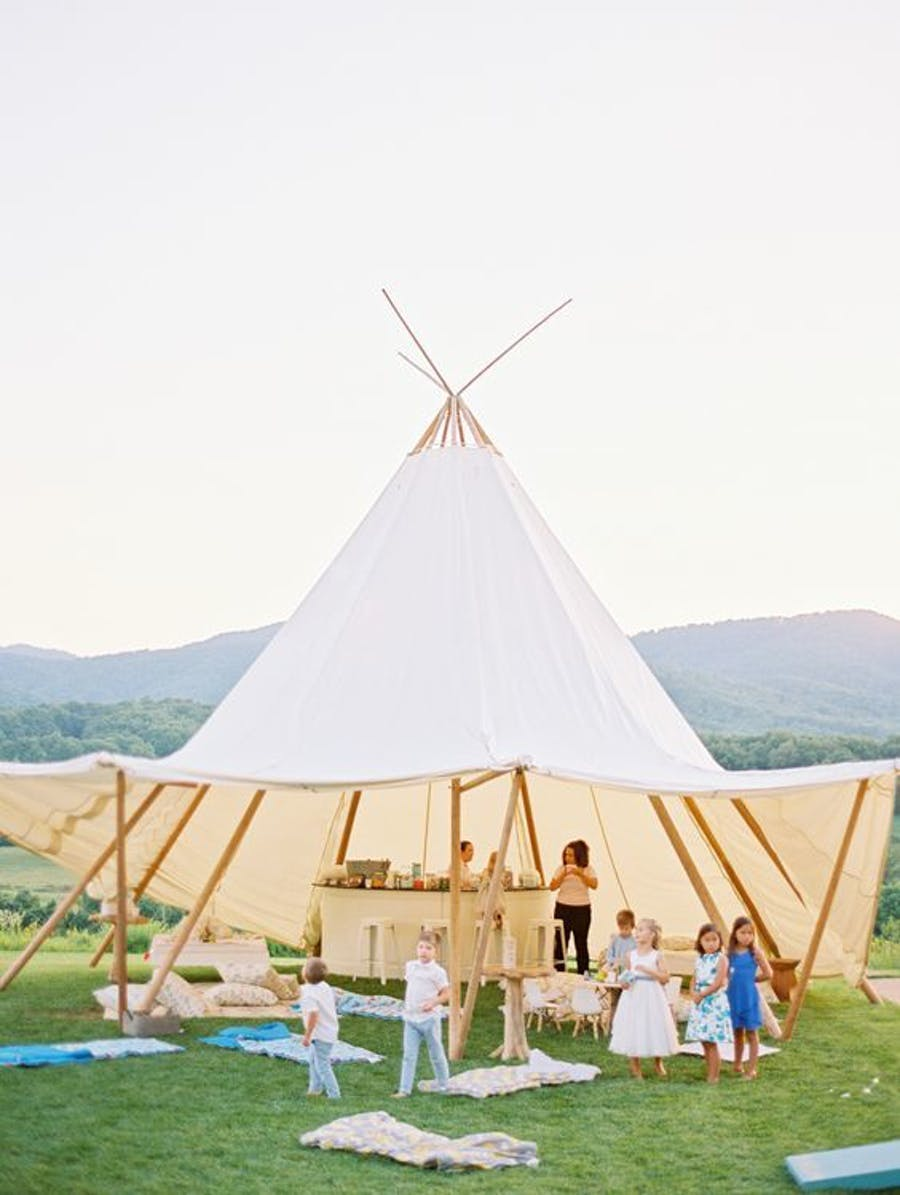 a white tee pee structure shades a raw wooden bar with kids playing under.