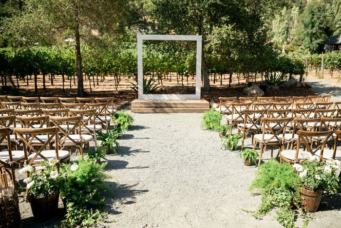 An outdoor wedding with wooden chairs and a square archway