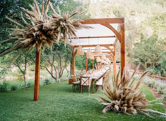 A cherry stained pergola with pampas grass accents. Underneath is a long table with white cushioned chairs on either side.