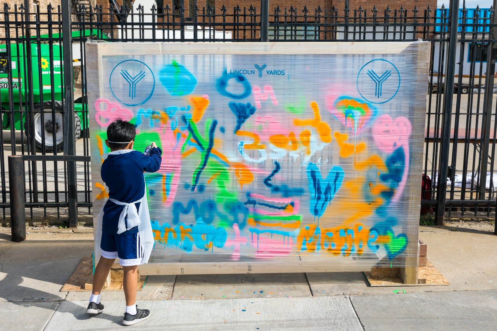boy creating canvas graffiti art at chicago community event