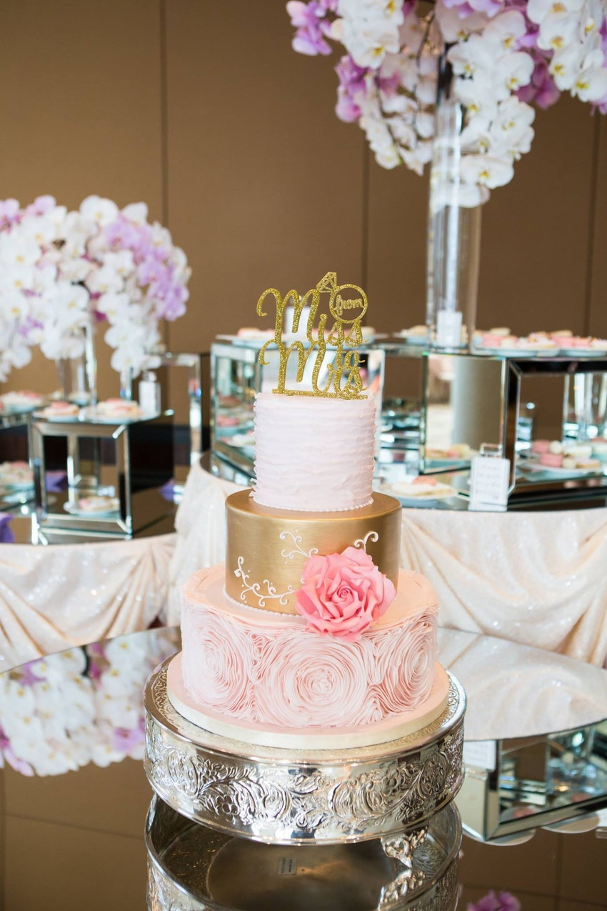 "A three-tiered blush and gold cake topped with a glittering gold scribe; ""from Miss to Mrs.,"" (the from was inside a carved out diamond ring) was highlight of the dessert station"