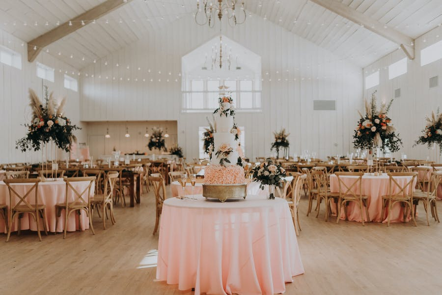 a pink linen table holds a tall wedding cake. In the background there are more pink linen tables with dark leafy arrangements as heightened center pieces. A skylight is on the back wall and fairy lights are throughout the venue.