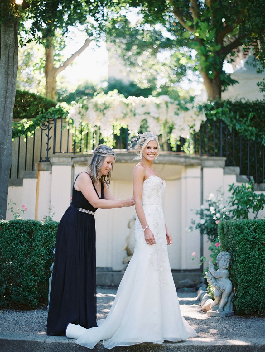 Maid of honor helping bride in her gown