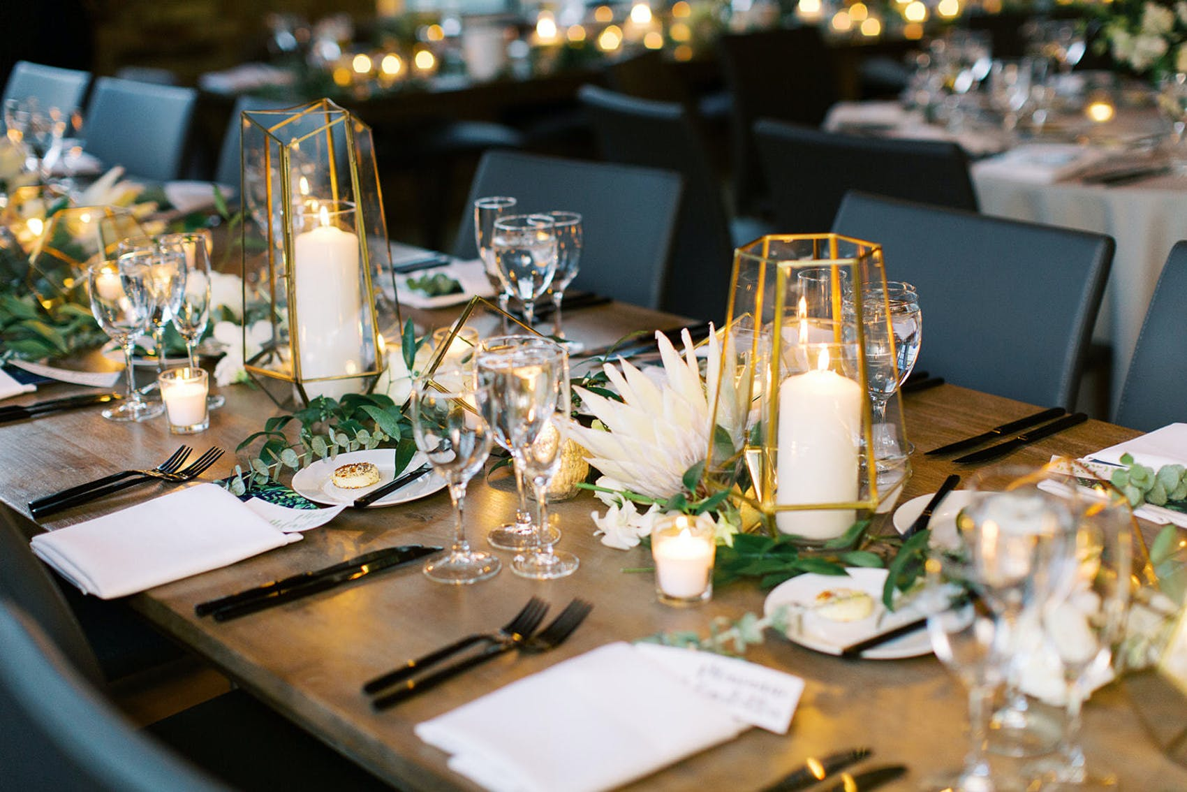 Two white candles and green and white flowers as centerpieces.