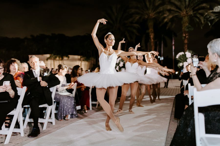 Ballerinas dance down the aisle while people sit on either side.