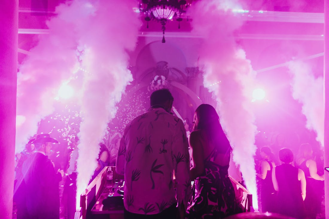 A couple in front of a pink illuminated room and smoke cannons.