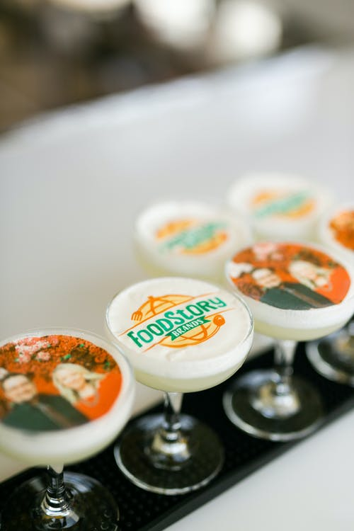 cocktails with pictures and logos floating on top