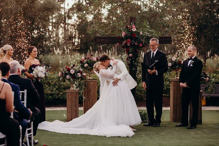 Bride and groom kiss at the altar with forest behind them and guests in front.