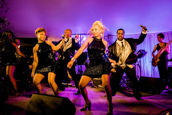Women wearing all black dresses dance in front of a stage band. Purple covers the walls