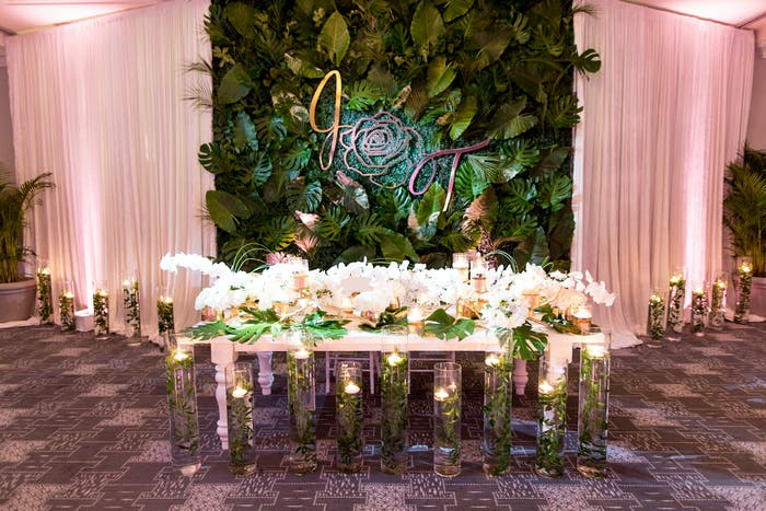 Candlelit ballroom shot of table with white orchids against backdrop of pale pink curtain and tropical leaves.