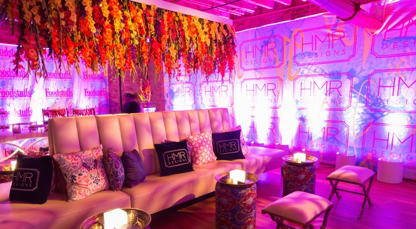 Inside Gallery 1 HMR Designs created lounge groupings with branded HMR elements and a bright floral piece that hung over the furniture.