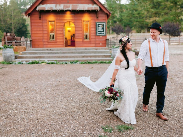 A couple walks away from a warmly lit cabin in the woods