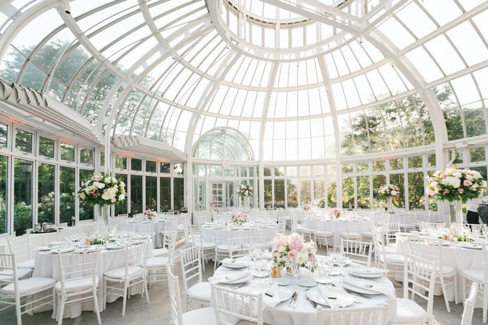 A large paned glass structure with all white furniture and short floral arrangements.