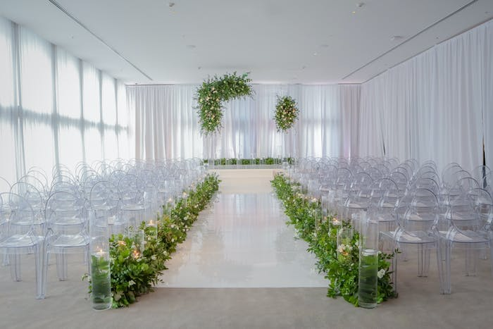 Clear chairs on either side of the aisle and an all white color palette. Greenery lines the aisle as well as drapes over the altar.