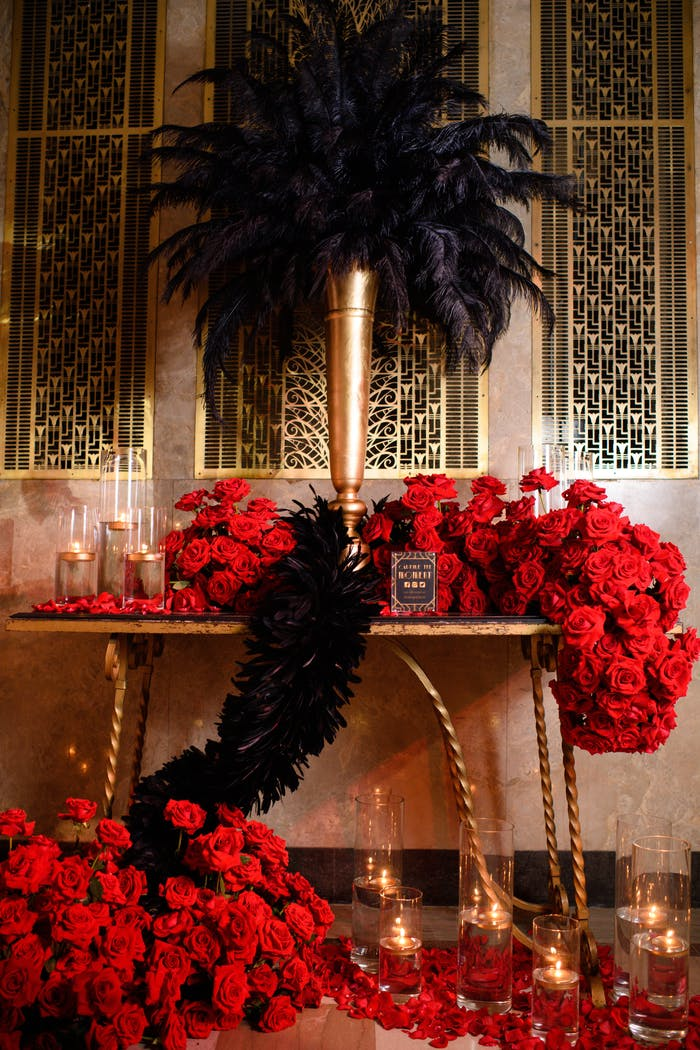 Art Deco-themed table with overflowing red roses, black-feathered centerpiece with gold vase, and candlelight.